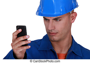 portrait of young blue collar reading sms against white...