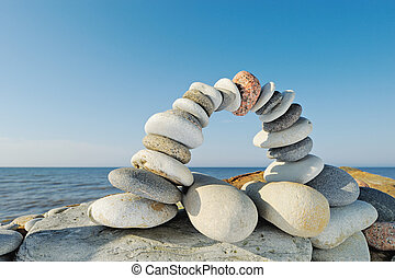 Stone Arch - Balancing of white pebbles on the seashore