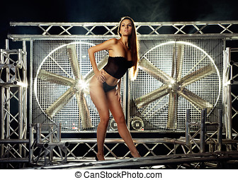 very sexy and beautiful top model on a stage posing with a huge turbo ventilator behind her were the smoke is coming and lights are coming trough