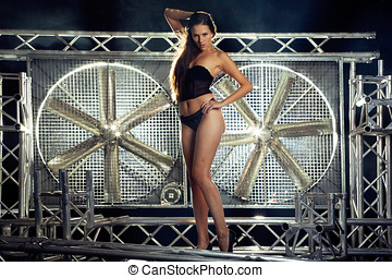 very sexy and beautiful top model in black lingerie on a stage posing with a huge turbo ventilator behind her were the smoke and stage lights are coming trough