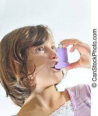 girl using an inhaler for asthma