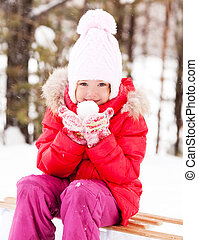 girl with a snowball - happy little girl on the sledge with...