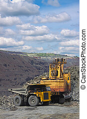 Opencast mining - Excavator loading iron ore into the heavy...
