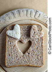 Bread hearts on Bread Board - Overhead shot of white and...