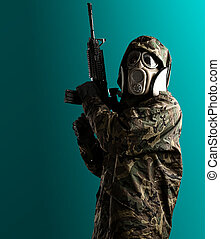 young soldier - soldier with camouflage coat, rifle and gas...