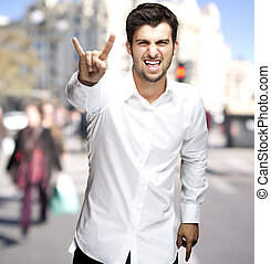 portrait of young man doing rock symbol at city