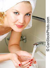 young woman washing her face - beautiful happy young woman...