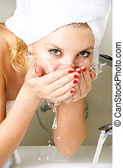 beautiful girl washing her face - beautiful young woman...
