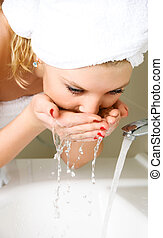 young woman washing her face - beautiful young woman washing...