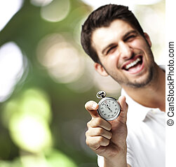 man holding stopwatch - portrait of young man holding a...