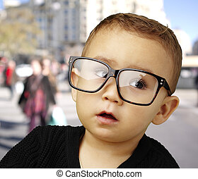 portrait of kid wearing glasses at crowded city