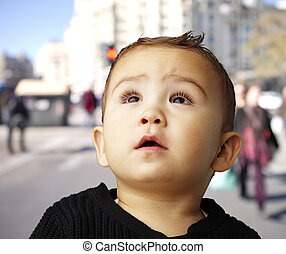 portrait of a handsome kid looking up against at crowded street