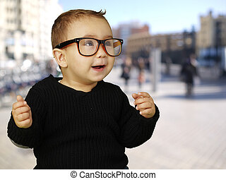 portrait of adorable kid wearing vintage glasses at a crowded st