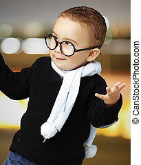 portrait of adorable kid wearing glasses gesturing doubt at...