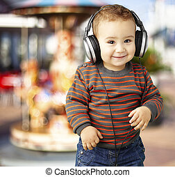 portrait of a handsome kid listening to music and smiling agains