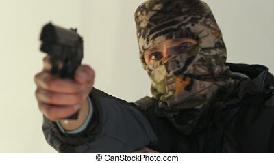 terrorist with pistol - masked man shooting with a handgun