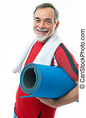 Senior man in gym - Senior man with a towel around neck...