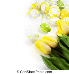 easter eggs with yellow tulip flowers isolated on white...
