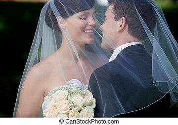 Bride And Groom Kissing Under Veil Holding Flower Bouquet In...