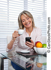 Mature Woman Using Phone - Smiling mature woman using cell...