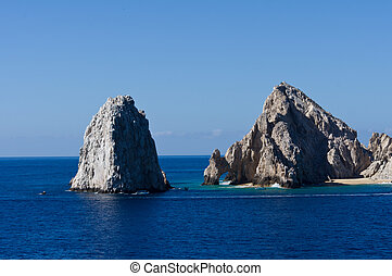 Rock formations including El Arco rise from the ocean