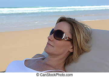 portrait of a woman resting on the beach