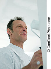 Happy man using a paint roller
