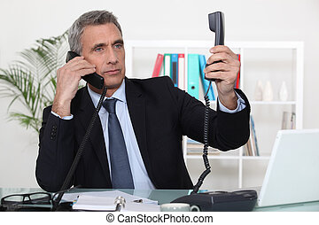 Businessman on two telephone calls