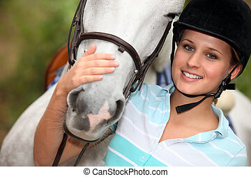 Young woman caressing her horse