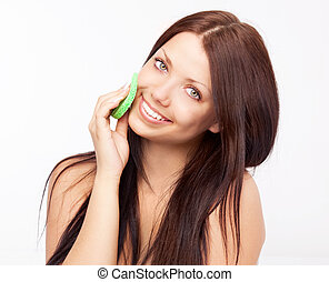 woman cleaning face - beautiful young brunette woman...
