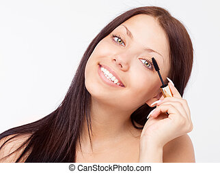 woman applying mascara - beautiful young brunette woman...