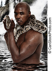 Attractive Fit Black Man with Boa Constrictor Standing in Lake
