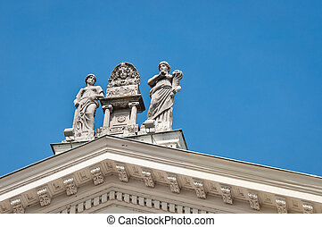 Roman statues on a roof against blue sky