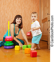 Happy mother and baby plays   at home interior