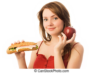 young woman choosing between an apple and hot dog -...