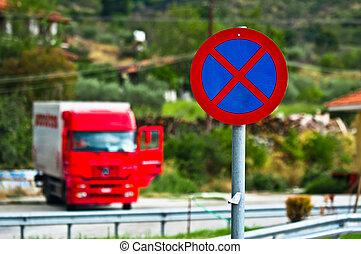 Traffic sign with parked truck in the background