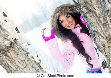 girl throwing a snowball - pretty young brunette woman...