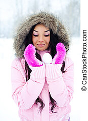 girl with a snowball - pretty brunette girl holding a...