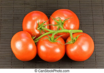 tomatoes on black tablemat - bunch of fresh tomatoes on...