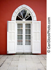 White door on red wall background
