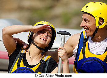 Happy couple rafting equipment - Happy couple with helmets...