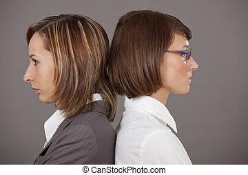 confrontation - two sad business women standing back on back...