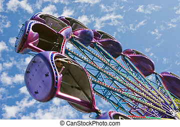 Popular attraction in park - a Ferris wheel on a background of the cloudy blue sky