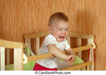 Crying baby of one year old in crib