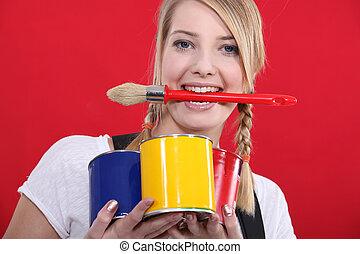 portrait of female painter holding brush between her teeth