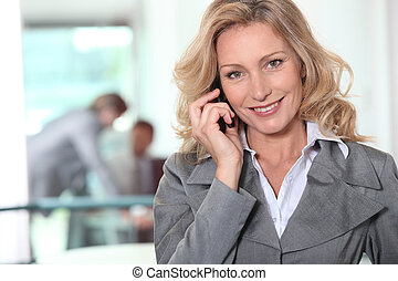 Businesswoman using a cellphone in an office