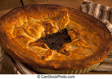Meat pie - A delicious home made meat pie on a wooden table...