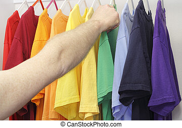 Picking Out a Shirt - Male arm and hand picking out a green...