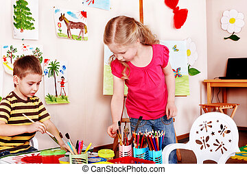 Child  draw paints in play room.