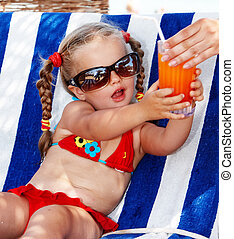 Child girl in glasses and red bikini drink juice. - Child...